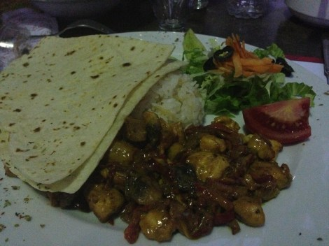 Chicken cooked in a curry sauce, served with lavaş (flatbread), rice and salad