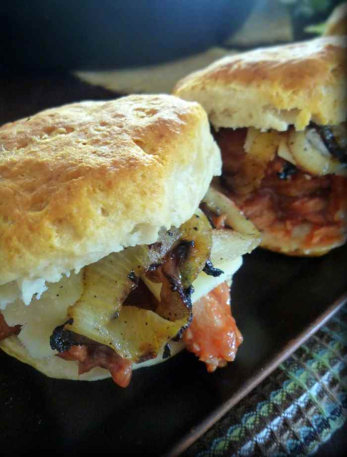BBQ'd Pork Sirloin Sliders on Biscuits is that delicious savory and sweet recipe that's made with chopped Pork Sirloin Roast, sweet bbq sauce, sharp white cheddar cheese, and caramelized onions, piled high on hot fresh buttermilk biscuits.