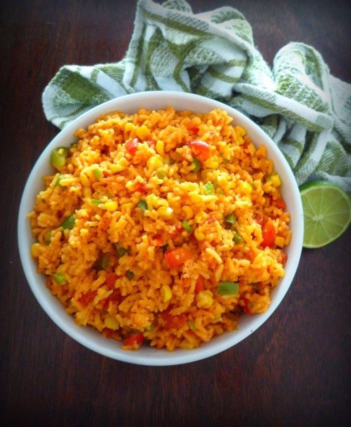 Mexican Rice with Corn is a flavorful yet simple and utterly delicious Mexican-Inspired recipe that pairs well with almost any of your favorite Mexican Dishes; combining long grain rice with fresh green bell peppers, red bell peppers, Spanish onion, minced garlic, organic non-GMO corn, and seasoned to perfection with Mexican Spices.