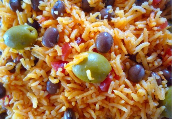 Rice with Pigeon Peas { Arroz Con Gandules } is one of my favorite Puerto Rican recipes usually served on Holidays and special occasions, made with long grain rice, Spanish tomato sauce, sofrito, pigeon peas, green olives, and seasoned with Sazon Seasoning with achiote, kosher salt, and freshly ground peppers.