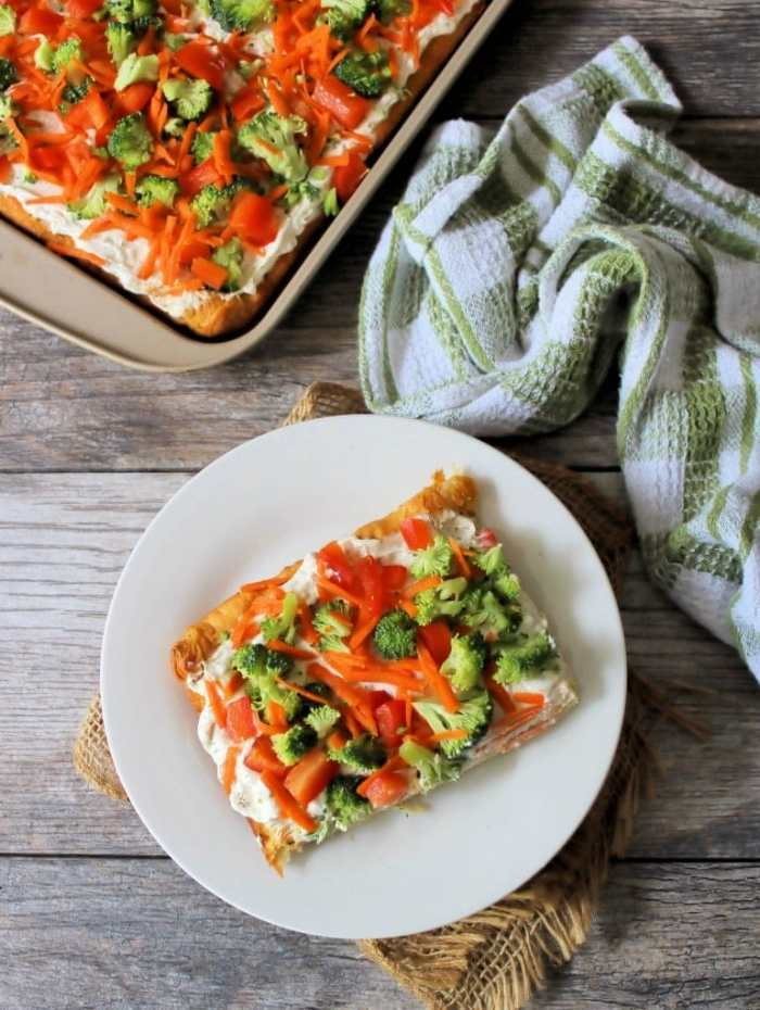 Fresh Veggie Pizza is one of the best retro recipes to this day, with all of those fabulous textures on top of a soft fluffy crescent roll crust, slathered with cream cheese, herbs, and organic crisp fresh veggies. It's guaranteed to fly off the table in no time flat this season.