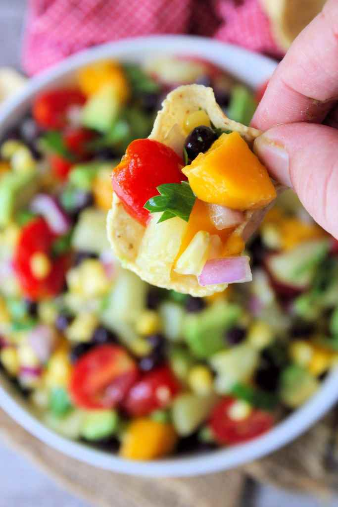 Make the perfect crowd pleaser in just a matter of minutes with this deliciously flavorful fresh-tasting Black Bean and Corn Salsa with avocados, pineapple, and mango that your family and friends will enjoy on tortilla chips, tacos, salads, grilled chicken, fish, or even steak.
