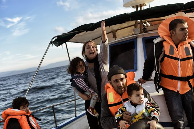 Syrian Kurdish refugees are recued by Greek fishermen as the boat they had boarded sinks off the Greek island of Lesbos after crossing the Aegean sea from Turkey on October 30, 2015. AFP PHOTO / ARIS MESSINIS (Photo credit should read ARIS MESSINIS/AFP/Getty Images)