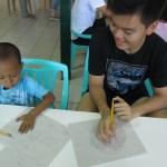 Joshua Emmanuel Tan checking Mhico's art work.