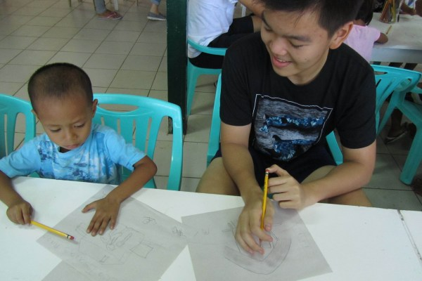 Joshua Emmanuel Tan checking Mhico's art work.