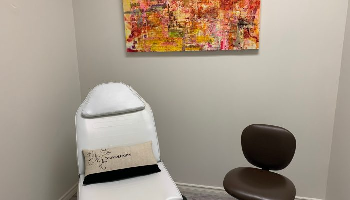 A treatment bed and chair in a room of Port Hope Complexion Medspa