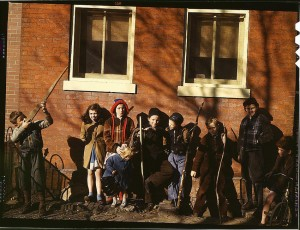 Children aiming sticks as guns, lined up against a brick building. Washington, D.C.(?), between 1941 and 1942. Reproduction from color slide. Photographer Unknown. Prints and Photographs Division, Library of Congress