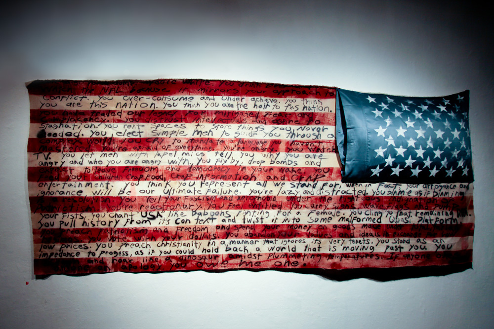 untitled Flag. Below is the text on this piece. You're big. You're dumb. You're white. You drink beer and watch the NFL because it mirrors your approach to conflict. You over-consume and under achieve. You think you are this nation. You think you are the heir to this nation. You have traded our legacy for mitigated fear and complacency. You distrust intellectuals and aspire to stagnation. You rent spaces to store things you never needed. You elect simple men to guide you through a complex world. You cry to mandate a language you haven't mastered. You're afraid of everything. You're angry. You watch TV You let men with lapel mics tell you why you're angry and who you're angry with. You fly by, drop bombs and expect to leave freedom and democracy in your wake. You feed your children crap food, crap information and crap entertainment. You think you represent all we stand for, when in fact, your arrogance and ignorance  will be our ultimate failure. You're lazy and distracted. You blame as if blaming is a resolution. You veil your fascism and xenophobia under the righteous indignation of patriotism. You're reactionary. You feel entitled. You carry signs and wave flags and pump your fists. You chant USA like baboons fighting for a female. You cling to that remaining DNA. You pull history from it's context and twist it into some malformed quasi platform. You preach patriotism and freedom and spend your money on goods made under totalitarian regimes. You vote with your dollars. You abandon your values and ideals in exchange low low prices. You preach christianity in a manner that ignores it's very tenets. You stand as an impedance to progress, as if you could hold back a world that is moving past you. You scream and roar like a dinosaur amidst plummeting temperatures. and if anyone owes anyone an apology you owe me one.