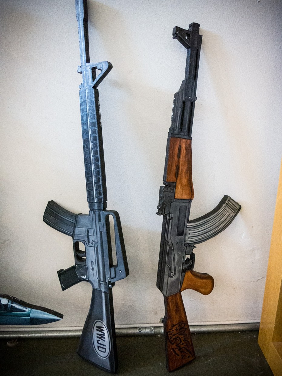 """The AK-47 """"Heathen Hunter"""" and """"Infidel Eliminator"""" waiting to be mounted on display."""