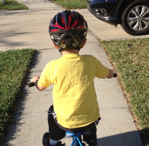 young child on bicycle outdoors