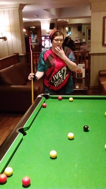 woman standing behind pool table