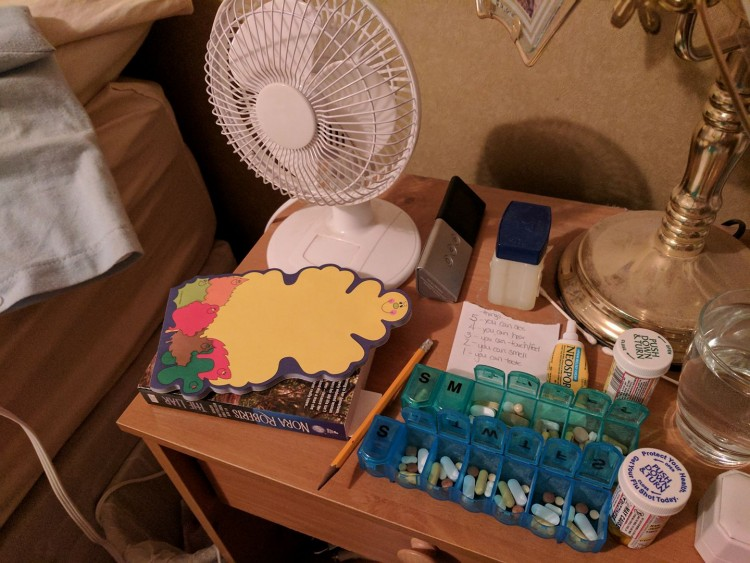 table of pills, fan, books, notepad
