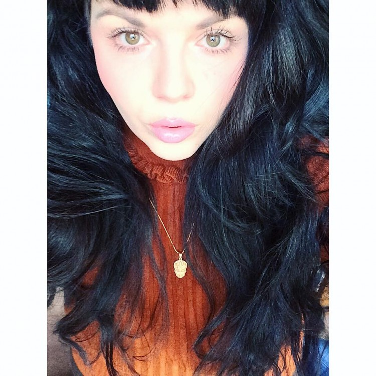 woman with long black hair and orange sweater