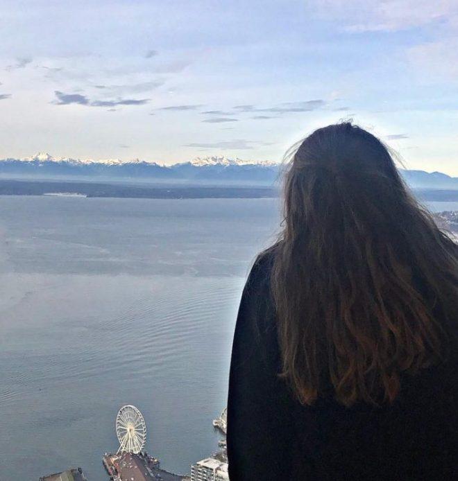 woman looking at ocean by Seattle