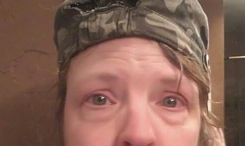 close-up photo of a woman's face. she's wearing a green camo hat and is crying