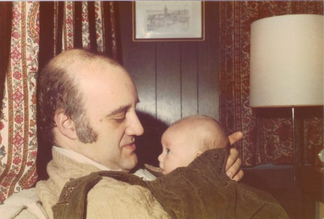 man holding very small baby with a very loving look on his face