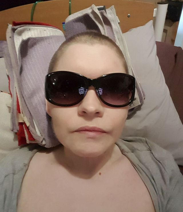 woman lying in bed wearing sunglasses