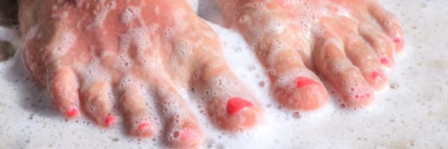 woman's feet standing in soapy water of a shower