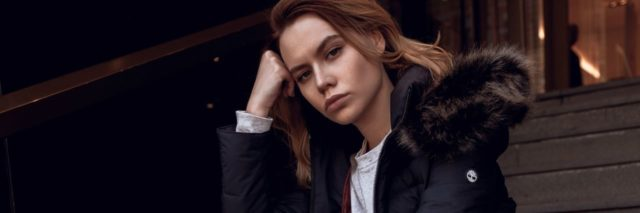 woman sitting on concrete stairs and wearing a black puffy jacket