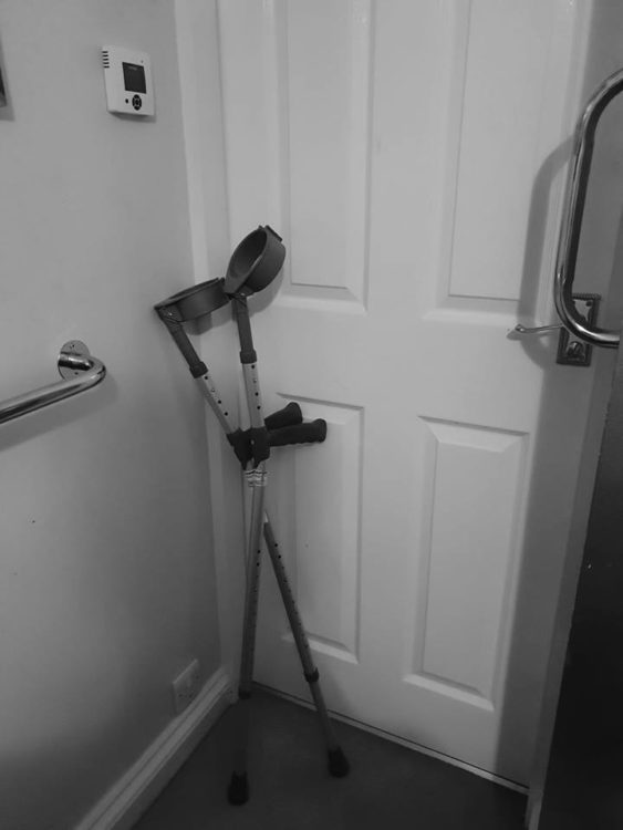 forearm crutches standing in the corner of a room by a door