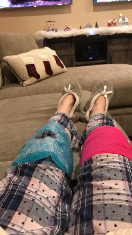 woman sitting on her couch with her legs out straight. she's wearing pajama pants and slippers and has ice packs on her knees