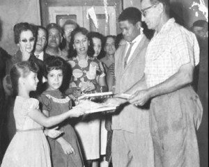 Griselda Aguilera, left at age 7 in 1961, hands literacy certificate to worker she taught to read and write. Aguilera spoke about literacy campaign and Cuban Revolution to hundreds on college campuses, churches and union halls during recent U.S. tour.