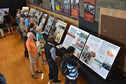 Participantes estudian exhibiciones que ilustran participación del partido en la lucha de clases y sobre eventos en desarrollo en la política mundial.