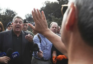 Mati resident Giannis Kardiakos, right, confronts Greek Defense Minister Panos Kammenos July 26, after forest fire killed 91. Government organized no evacuation, blamed area residents.