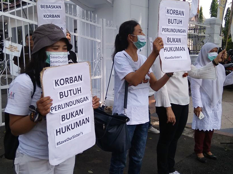 "Protest at Jambi, Indonesia, prosecutor's office July 26 demanding release of Wa, teenager imprisoned for having an abortion. Signs says, ""The victim needs protection, not punishment."""