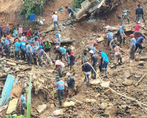 Miners join rescue workers to dig out victims buried in mudslide in Itogon, Philippines.