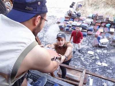 """Volunteers saving books from Mosul University library after IS burned it to the ground. """"We want to bring life to Mosul,"""" Al-Madany said."""