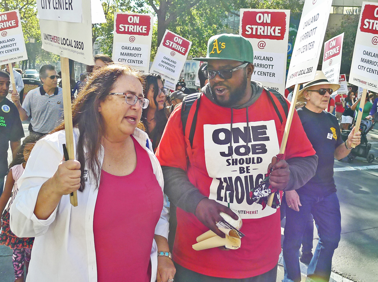 Laura Garza, Socialist Workers Party candidate for governor of California, walks hotel workers' strike picket line outside Oakland Marriott City Center with striker Jason Russell Oct. 20.