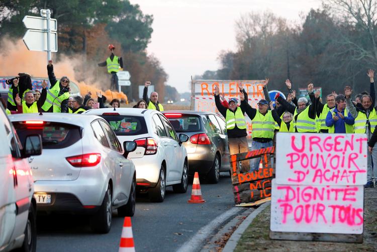 """""""Chalecos amarillos"""", trabajadores de pueblos pequeños y del campo, ganan apoyo en Cissac-Medoc, Francia, 5 de diciembre. Cartel dice: Urgente. Poder adquisitivo. Dignidad para todos."""