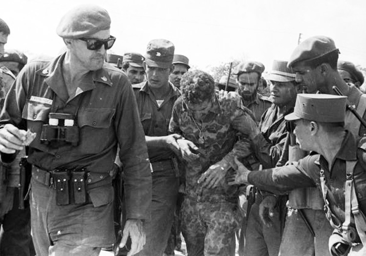 Above, José Ramón Fernández, left, leading Cuban forces against April 1961 U.S.-organized Bay of Pigs invasion. Behind him, revolutionary soldiers aid captured mercenary. Fernández carried out many responsibilities from training first militia battalions to helping transform education system. Left, José Ramón Machado Ventura, second secretary of Communist Party of Cuba, speaking at tribute to Fernández. Machado was medical doctor and combatant of Rebel Army during revolutionary war that overthrew Batista dictatorship in 1959.