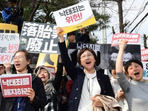 """Rally in Seoul April 11 celebrates South Korea's high court ruling that country's ban on abortion is unconstitutional. Signs say, """"Abortion law should be abolished"""" and """"is unconstitutional."""""""