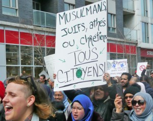 """Sign reads, """"Muslims, Jews, atheists or Christians. All citizens!"""" Thousands protest in Montreal April 7 against bill banning public sector workers from wearing religious symbols at work."""