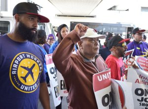 """Chanting """"One job should be enough!"""" airport workers as well as Sky Chef and Gate Gourmet workers picket together at San Francisco International Airport for higher wages, new contracts."""