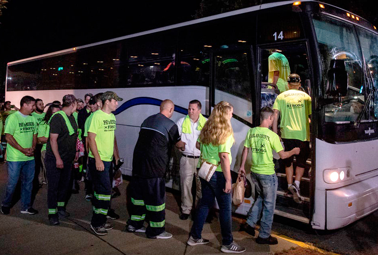 """Miners in Harlan County, Kentucky, get on bus to attend Blackjewel Coal bankruptcy hearing Aug. 5 in Charleston, West Virginia, wearing T-shirts saying """"Pay the miners first, lawyers last."""""""