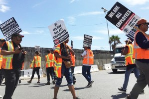 """Truck drivers employed by NFI Industries' California Cartage picket port in Wilmington, California, Sept. 9 during weeklong strike, demand to be treated as workers, not """"contractors."""""""