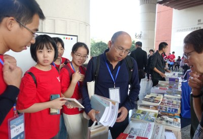 Conference participants gather around Pathfinder Press literature table.