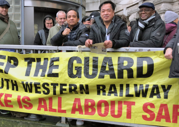Picket at Waterloo station, London, during December strike against South Western Railway in defense of guard jobs, safety for rail workers and passengers. Fight by workers to get UK out of EU took place against backdrop of deepening capitalist crisis, growing disdain of Labour Party.