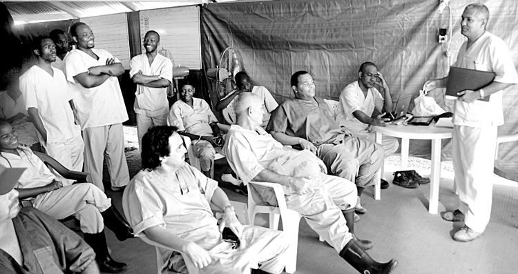 """Cuban doctors and Guinean staff at shift change at the Coyah treatment center in Guinea, January 2015. """"As they reported for duty, Cubans always made jokes,"""" writes Ubieta. """"It lifted their spirits and those of patients and colleagues."""""""