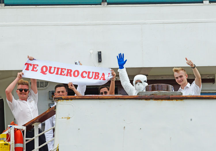 "MS Braemar crew members hold sign, ""I love you Cuba,"" after Cuban government let ship dock March 18 with passengers with coronavirus, after other Caribbean nations denied it entry."