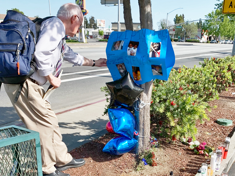 Joel Britton, SWP candidate for Congress, pays respects to Steven Taylor at memorial site set up by his family near Walmart in San Leandro, Calif., Cops gunned him down in store April 18.