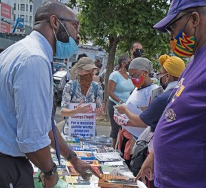 """SWP congressional candidate Willie Cotton, left, and SWP member Tamar Rosenfeld, wearing sign, talk with other participants at New York police brutality protest June 7. """"There's a thirst for books about Black struggle, women's emancipation, revolutionary history,"""" Cotton said."""