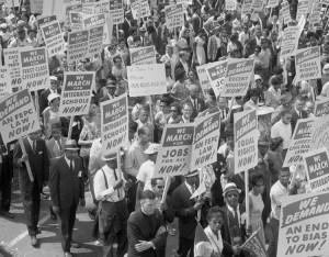 Marche de 1963 sur Washington pour des emplois et la liberté, dans le cadre du puissant mouvement de la classe ouvrière dirigé par des Noirs, qui a renversé le système de ségrégation de Jim Crow. Ce mouvement a aussi permis d'obtenir, l'année suivante, la Loi sur les droits civils, interdisant la discrimination à l'emploi, les congédiements et les promotions sur la base de la « race, de la couleur, de la religion, du sexe ou de l'origine nationale. »