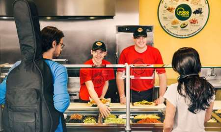 Burrito builder makes a burrito in line for a sycophantic customer.