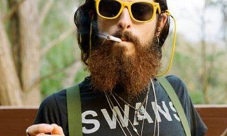 A hipster smokes weed on his porch.