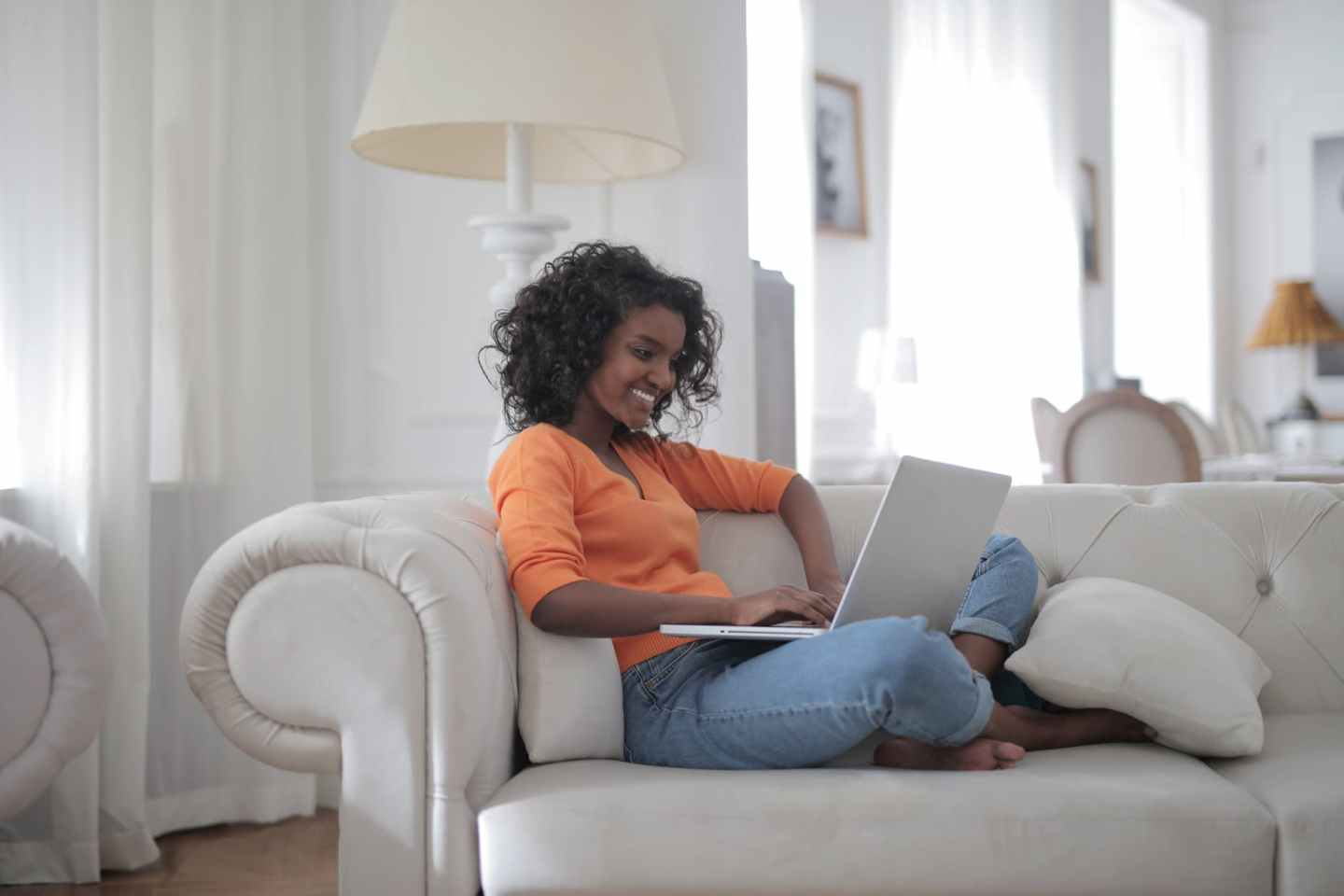 woman sitting on white couch using laptop computer - Representing working from home