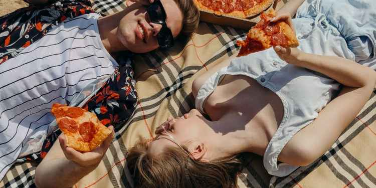 couple laying down and eating pizza